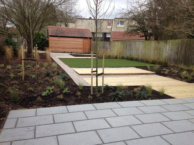 Contemporary garden with granite paving, decking and limestone gravel pathways and ornamental pear trees