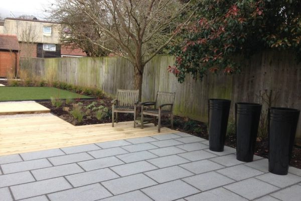 Garden with granite paving, decking ad tall circular planters