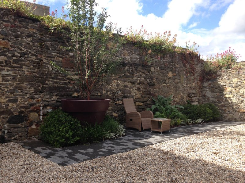 Walled garden featuring oversized planter and cherry tree