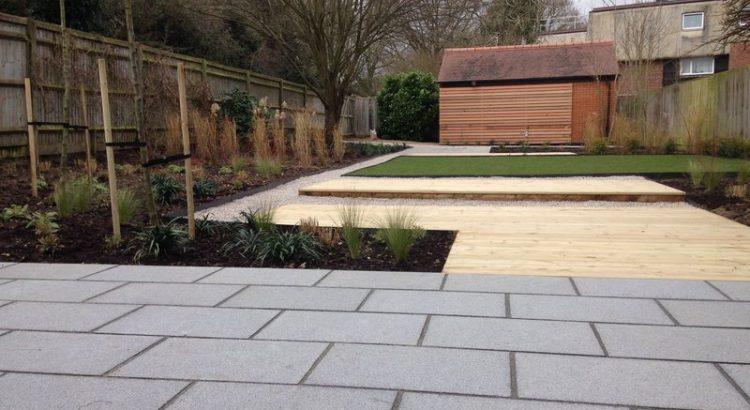 Landscaped garden of granite paving, a decking and limestone pathway, and western red cedar screen