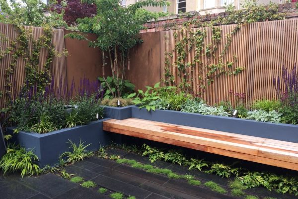 cedar bench and raised bed with ornamental cherry and water bowl